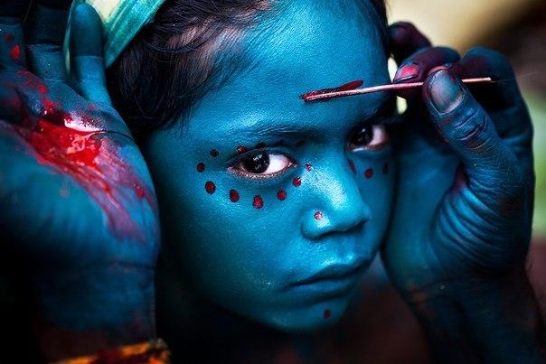 Божественный макияж на лице юной индийской девочки, наносимый в честь праздника Махашиваратри, посвящяемый божеству Шиве.