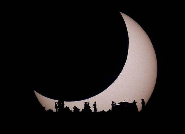 На фотографии изображено Солнце, частично закрытое с левой верхней стороны Луной, а снизу силуэтами землян, наблюдающих