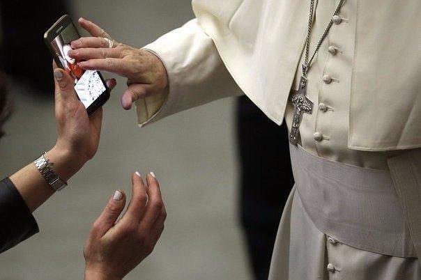 Папа Римский благословляет ребёнка по фотографии на смартфоне.